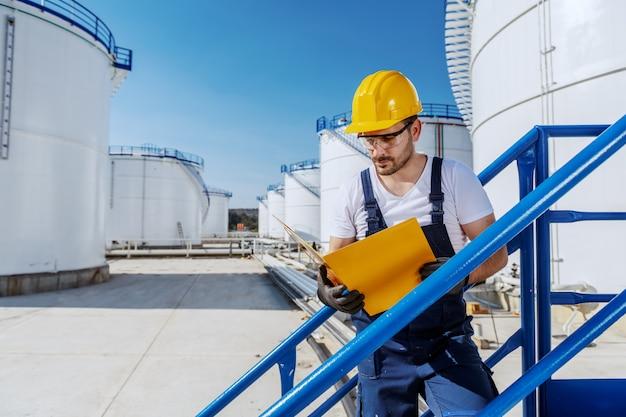 Pracowity przystojny kaukaski pracownik w kombinezonie iz hełmem na głowie stojący na schodach i patrząc na folder z dokumentami. produkcja oleju.