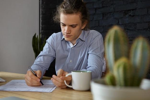 Pracowity skoncentrowany młody biznesmen w niebieskiej koszuli robi papierkową robotę w swoim biurze, popijając poranną kawę. koncepcja ludzie, praca, zawód, zawód, biznes i kariera. selektywna ostrość