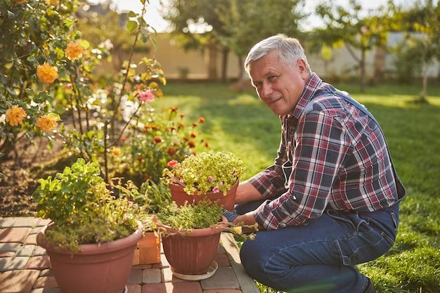 Pracowity starszy mężczyzna klęczy obok roślin doniczkowych w swoim ogrodzie, uśmiechając się do kamery