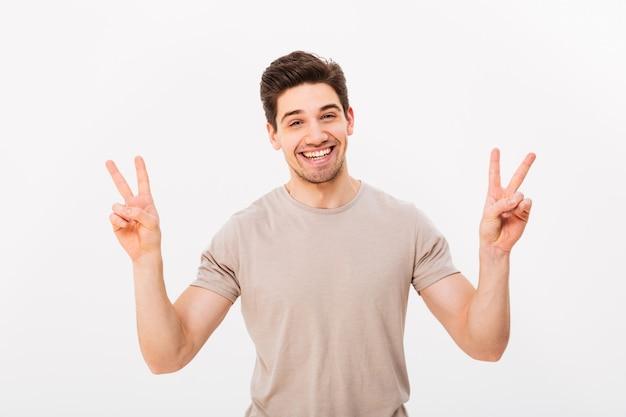 Pracowniana fotografia życzliwy faceta model gestykuluje pokoju symbol obiema rękami i wyraża radość, odizolowywający nad biel ścianą