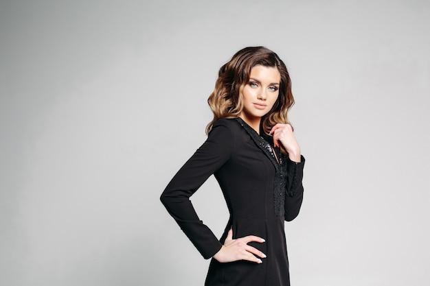Pracowniany portret brunetki dziewczyna w surowej czerni sukni z pozować, trzymający rękę na pasku i gładzący włosy, ono uśmiecha się przy kamerą na szarym tle. izolować