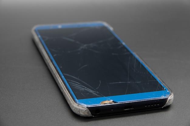 Pracowniany zbliżenia smartphone z krakingowym ekranem, odosobnionym na czarnym tle.