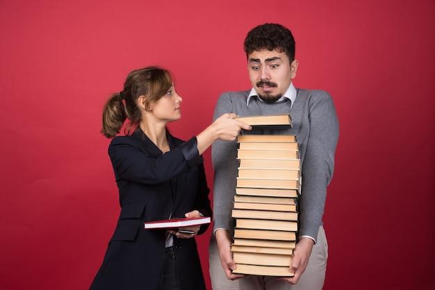 Pracownica biorąca od kolegi jedną książkę