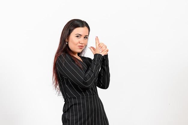Pracownica biura w ścisłym czarnym garniturze w posiadaniu broni poza na białym