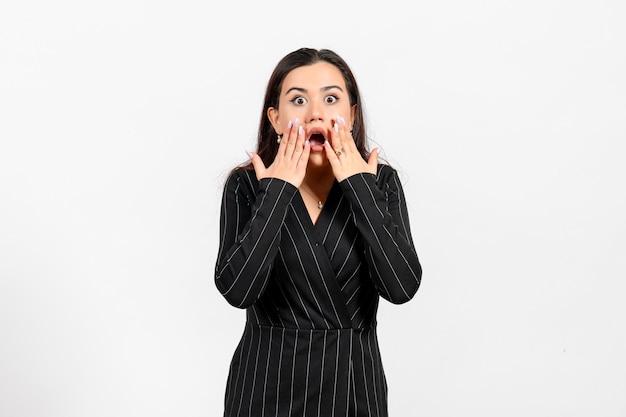 Pracownica biura w ścisłym czarnym garniturze z zszokowaną twarzą na białym tle