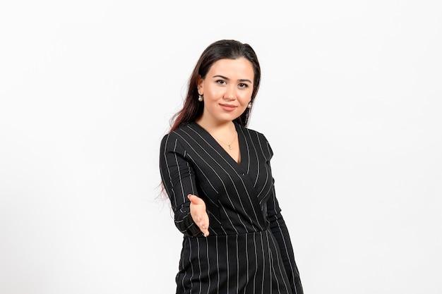 Pracownica biura w ścisłym czarnym kolorze, która chce uścisnąć dłoń na białym tle