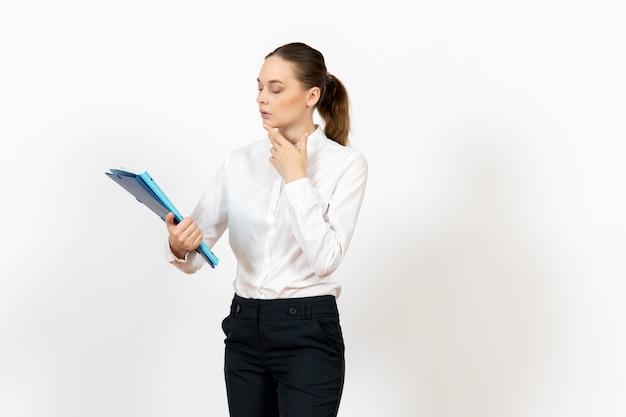 Pracownica biurowa w białej bluzce trzyma dokumenty na białym tle