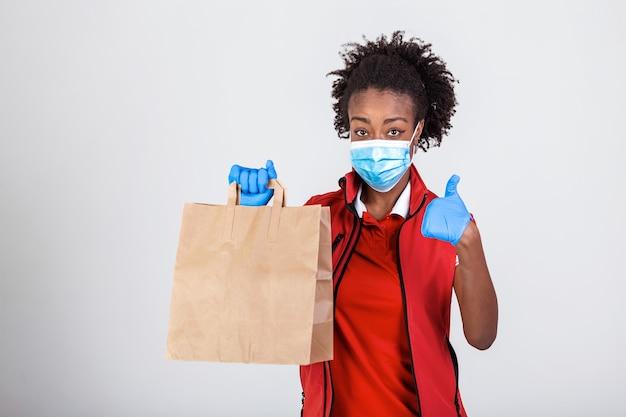 Pracownica dostawy w czerwonej koszulce jednolita maska rękawica trzyma pakiet papieru rzemieślniczego z jedzeniem