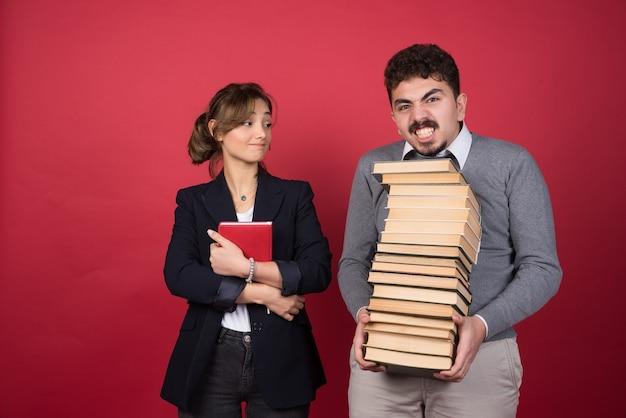 Pracownica patrząc na człowieka z pękiem książek
