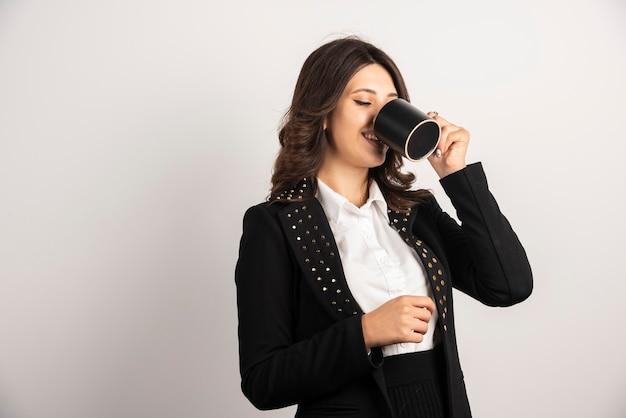 Pracownica pije zioła na białym