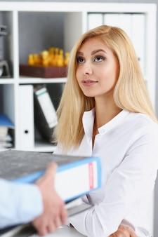 Pracownica pokazuje pakiet dokumentów kierownikowi
