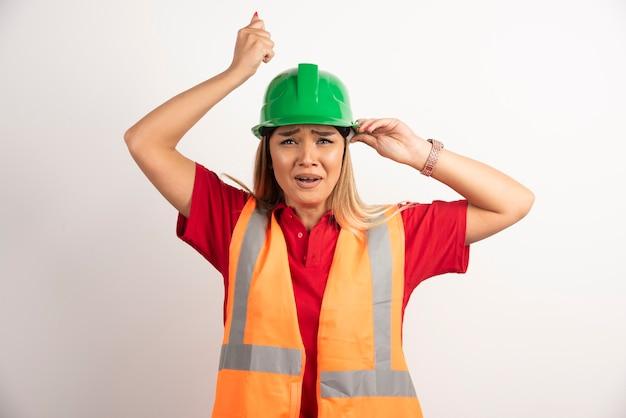 Pracownica pozowanie z hełmem i mundurem.