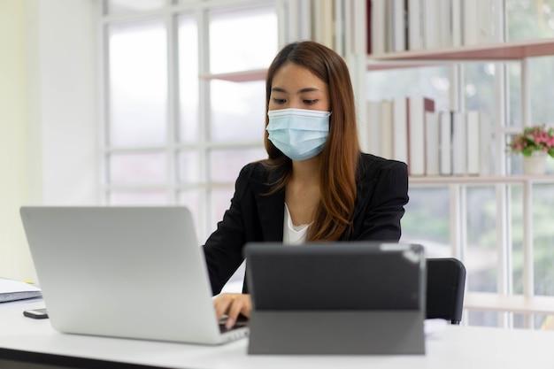 Pracownica pracująca w biurze do pracy po pandemii koronawirusa