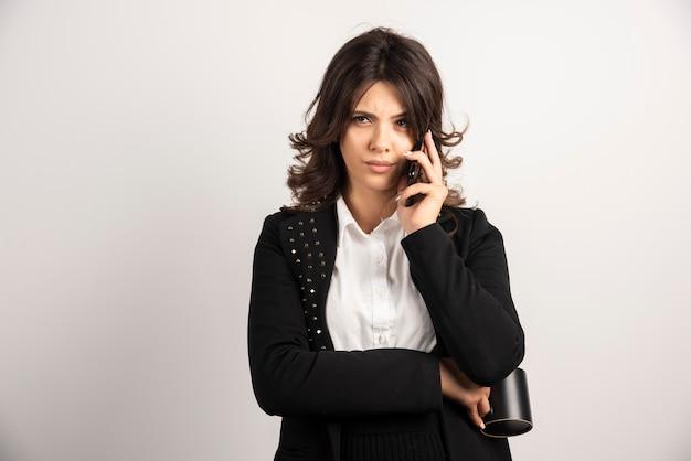 Pracownica rozmawia przez telefon na białym