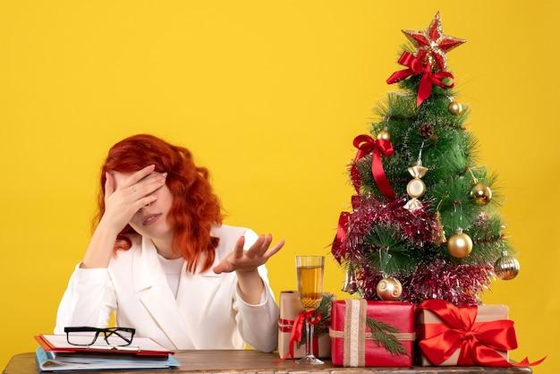 Pracownica siedzi za stołem z prezentami świątecznymi i drzewem podkreślił na żółto