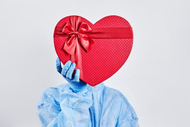 Pracownica służby zdrowia otrzymuje prezent walentynkowy w pracy. lekarz obchodzi walentynki w szpitalu. wesołych walentynek podczas wybuchu koronawirusa