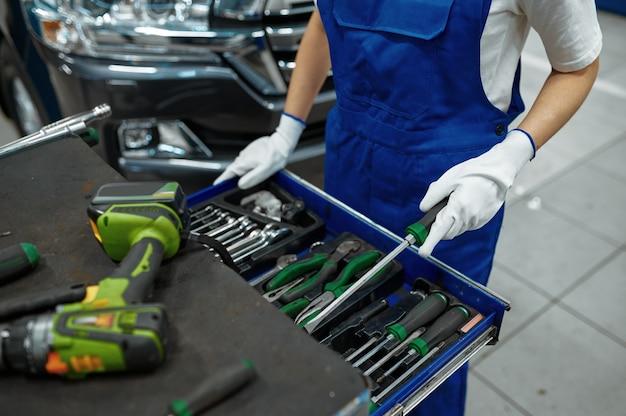 Pracownica stoi przy skrzynce narzędziowej, usługi samochodowe. garaż do naprawy pojazdów, kobieta w mundurze, wnętrze stacji samochodowej
