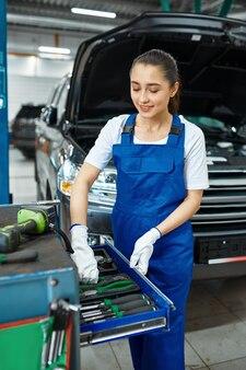 Pracownica stoi przy skrzynce z narzędziami, serwis samochodowy