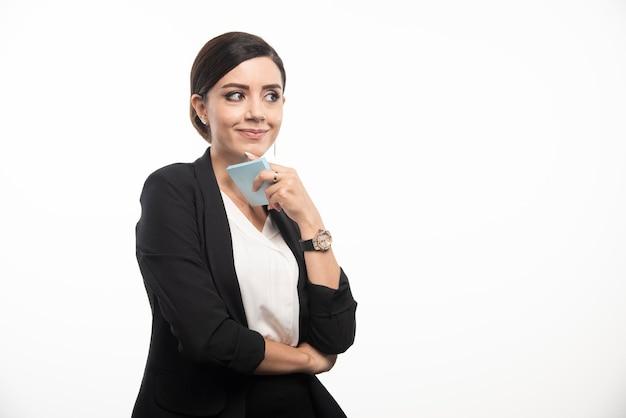 Pracownica trzyma notatnik na białym tle. zdjęcie wysokiej jakości