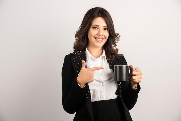Pracownica trzymająca herbatę i wskazująca na nią