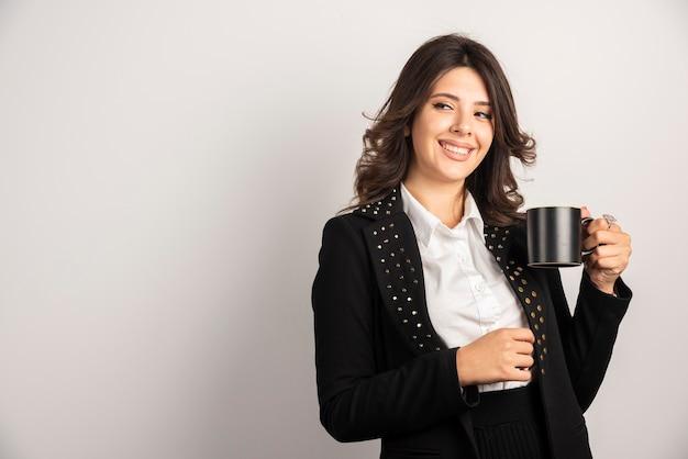 Pracownica trzymająca herbatę z radosnym wyrazem twarzy