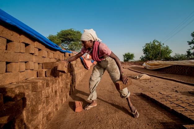 Pracownica układa cegły do następnego procesu w cegielni