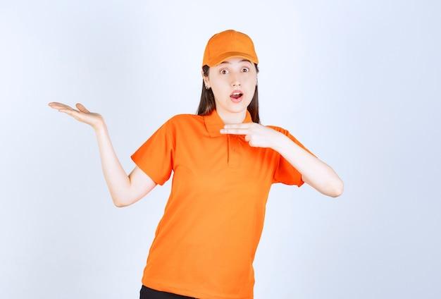 Pracownica usługowa ubrana w pomarańczowy mundur i pokazująca kogoś wokół.
