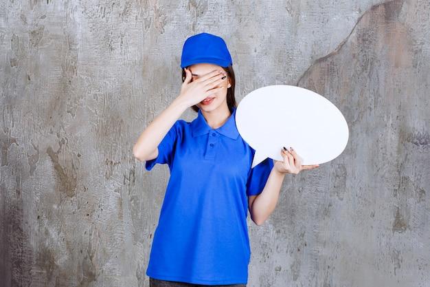 Pracownica usługowa w niebieskim mundurze trzyma owalną tablicę informacyjną i wygląda na zmęczoną.