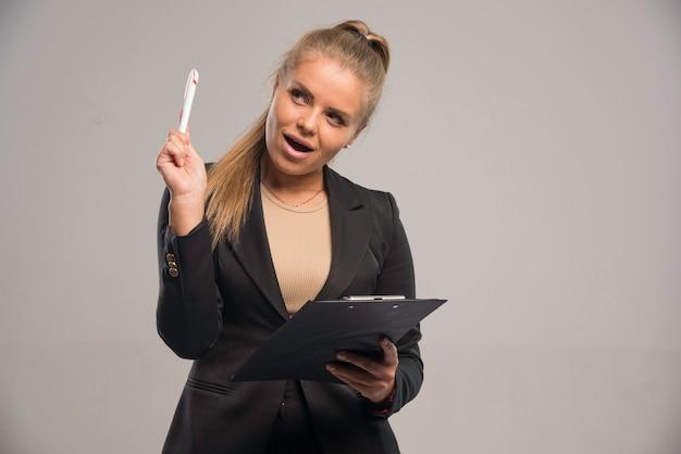 Pracownica w czarnym garniturze trzyma kontrakt i myślenia.