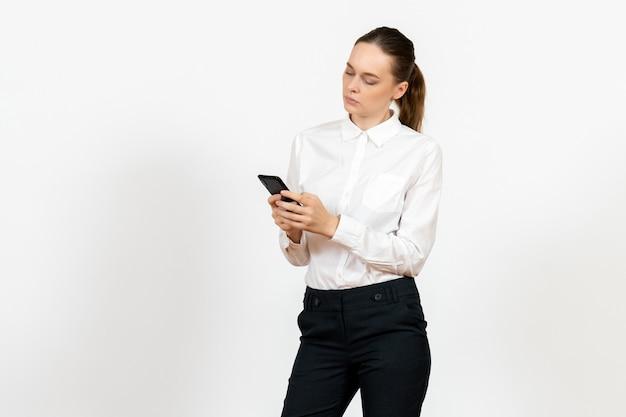 Pracownica w eleganckiej białej bluzce za pomocą swojego telefonu na białym tle