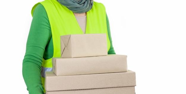 Pracownica w zielonej kamizelce stojącej w pobliżu wielu pudełek z pustym zamówieniem, koncepcja dostawy.