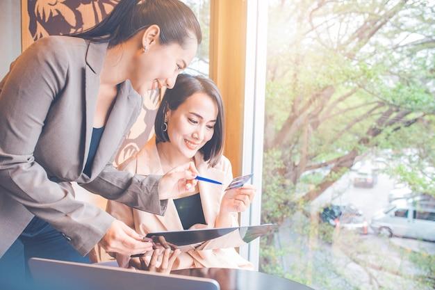 Pracownica wyjaśniająca klientom korzystanie z kart kredytowych. zadowoleni klienci na biurku mają komputery i telefony.