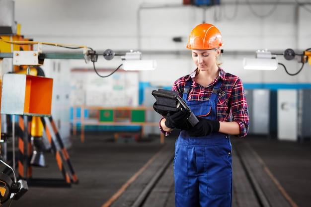 Pracownica z kasków wykonuje pracę w fabryce przemysłowej i szuka w kontrolerze przemysłowym