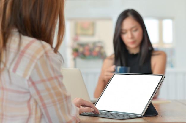 Pracownica za pomocą laptopa, aby przedstawić projekt kadrze kierowniczej siedzącej z kawą z tyłu.