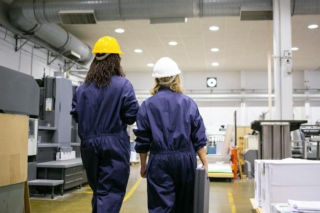 Pracownice fabryczne w kaskach i kombinezonach chodzą po hali produkcyjnej i rozmawiają, niosąc skrzynkę z narzędziami