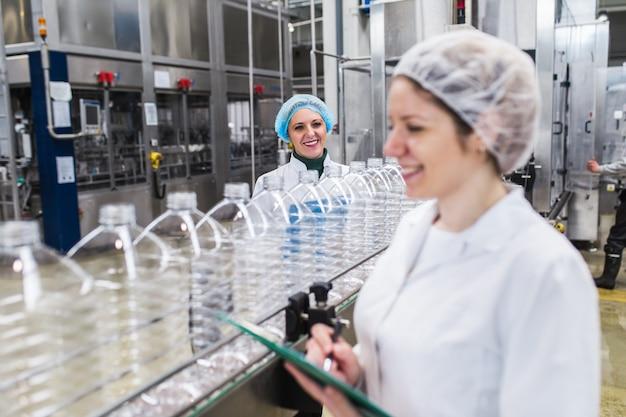 Pracownice w rozlewni sprawdzają butelki z wodą przed wysyłką