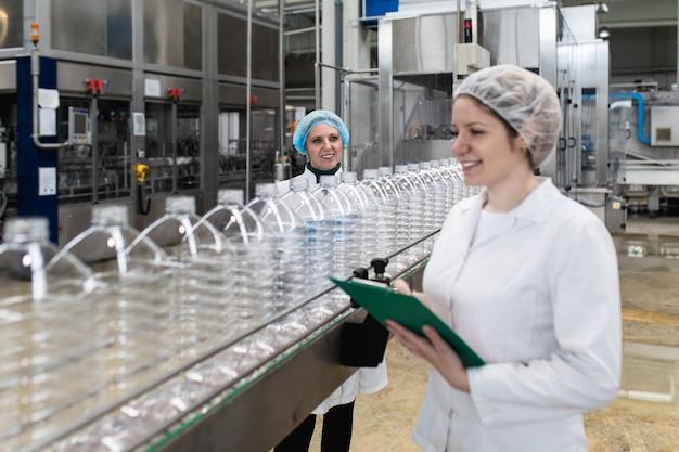 Pracownice w rozlewni sprawdzania butelek wody przed wysyłką. kontrola jakości inspekcji.