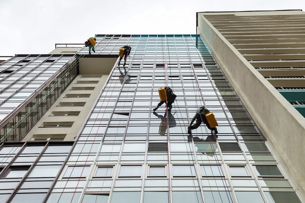 Pracownicy alpinizmu przemysłowego wiszą nad budynkiem fasady mieszkalnej podczas mycia przeszklenia elewacji zewnętrznej. robotnicy dostępu linowego wisi na ścianie domu. koncepcja przemysłowych prac urbanistycznych. skopiuj miejsce