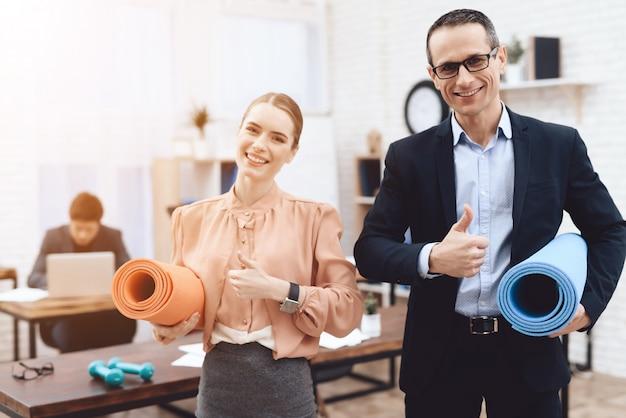 Pracownicy biura trzymają maty gimnastyczne i zegarek w aparacie.