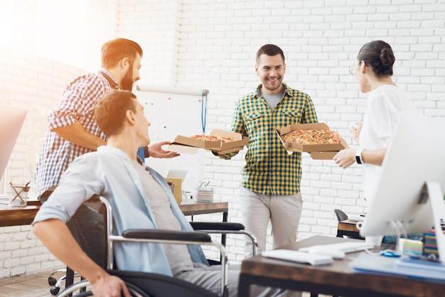 Pracownicy biurowi i mężczyzna na wózku inwalidzkim jedzą pizzę