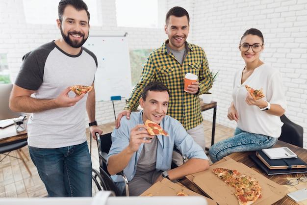 Pracownicy biurowi i mężczyzna na wózku inwalidzkim jedzą pizzę.