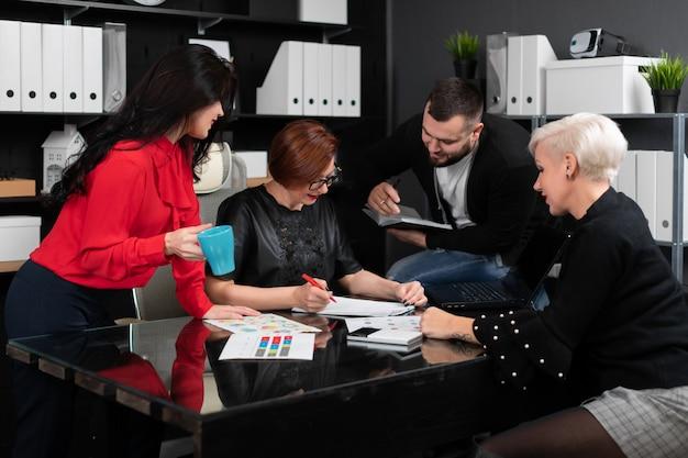 Pracownicy biurowi omawiają swój projekt nad filiżanką herbaty