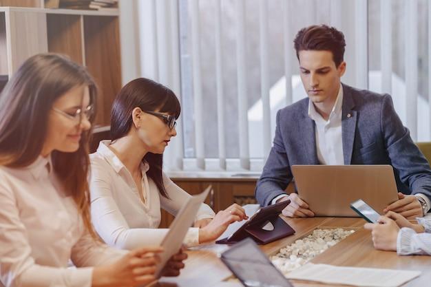 Pracownicy biurowi organizują spotkanie przy jednym biurku dla laptopów, tabletów i papierów, na tle dużego telewizora na drewnianej ścianie