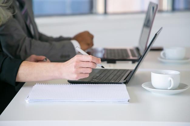 Pracownicy biurowi piszą notatki, używając laptopa przy stole z filiżankami kawy. zbliżenie dłoni, przycięty strzał. koncepcja edukacji lub komunikacji cyfrowej