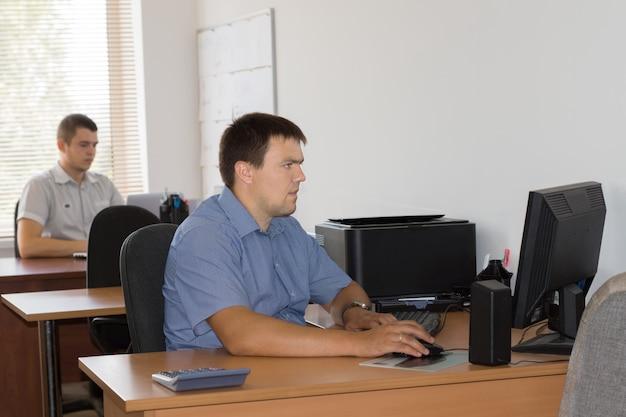 Pracownicy biurowi płci męskiej w średnim wieku w wyznaczonym miejscu przy stole zajęci pracą przy komputerze.