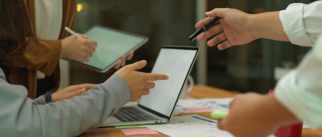 Pracownicy biurowi pracujący razem z makietami urządzeń cyfrowych i papierkową robotą w sali konferencyjnej
