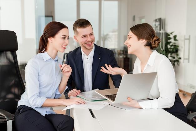 Pracownicy biurowi robią wspólnie projekt i śmieją się z przerwy w nowoczesnym budynku firmy
