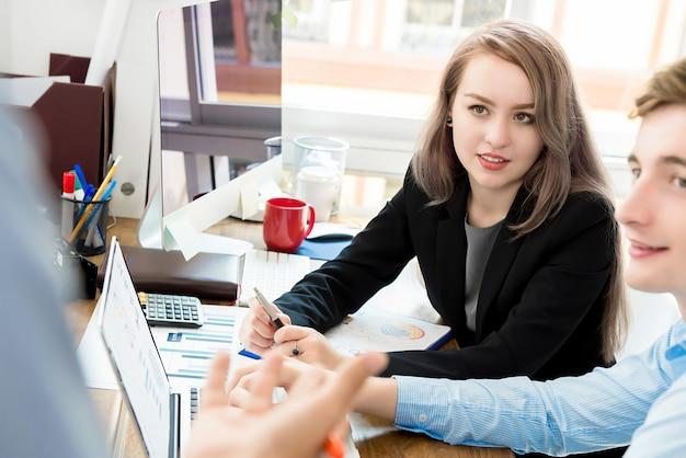 Pracownicy biurowi słucha ich kolega przy pracującym biurkiem