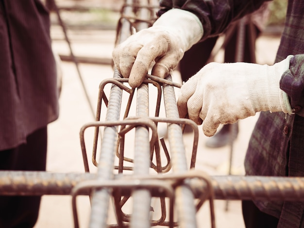 Pracownicy budowlani instalują stalowe pręty w kolumnie z betonu zbrojonego