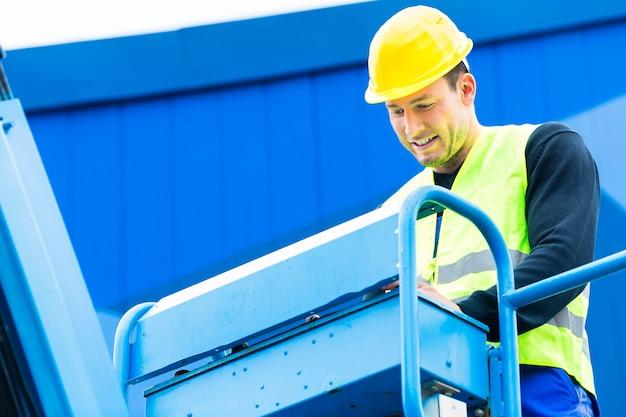 Pracownicy budowlani lub operator dźwigu na placu budowy prowadzący hydrauliczną rampę podnoszącą z pulpitem sterowniczym